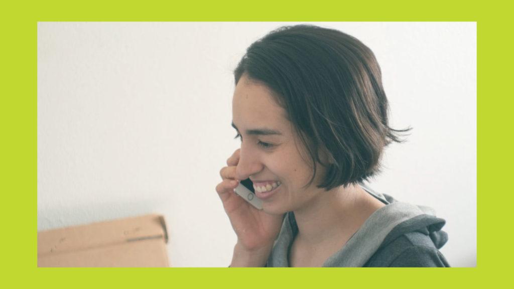 A smiling woman talks on the phone | Une femme souriante parle au téléphone