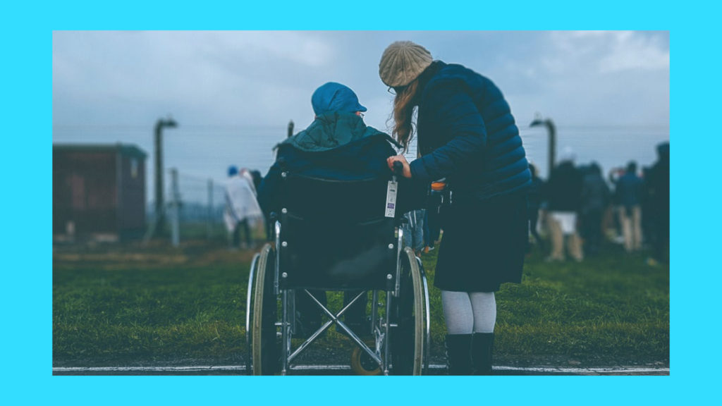A young lady helps an elderly lady in her wheelchair