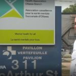 CMHA Ottawa Executive Director Tim Simboli stands in front of sign