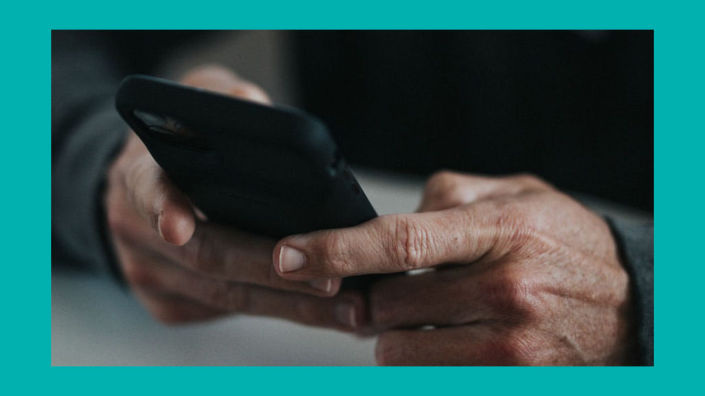 A man's hands holding a smartphone