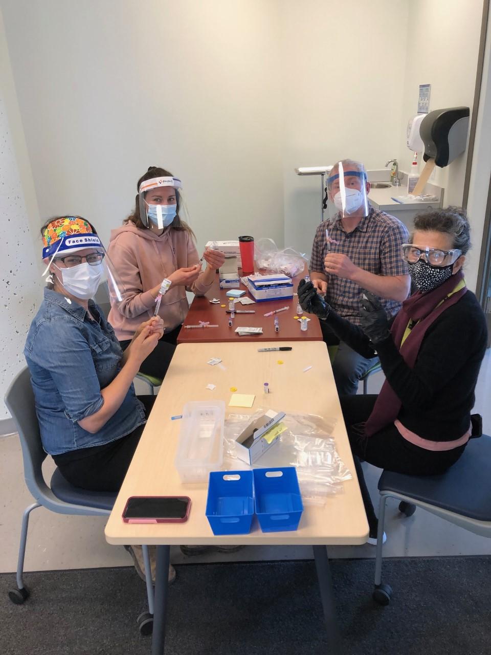 Four nurses sit around a table preparing vaccines